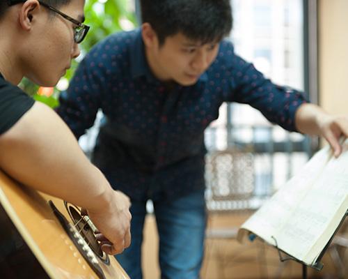木鱼音乐老师正在悉心的教学生弹吉他